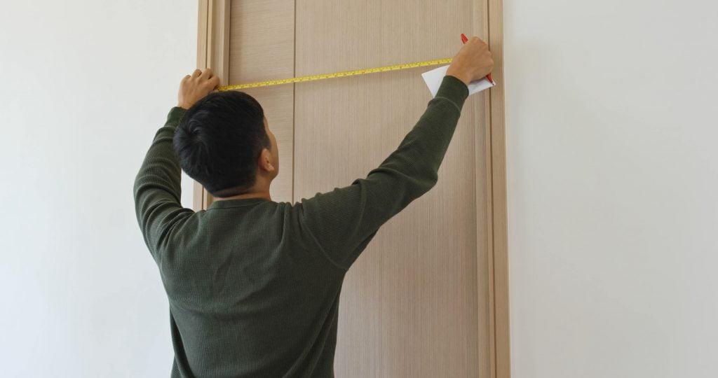 man measure door size
