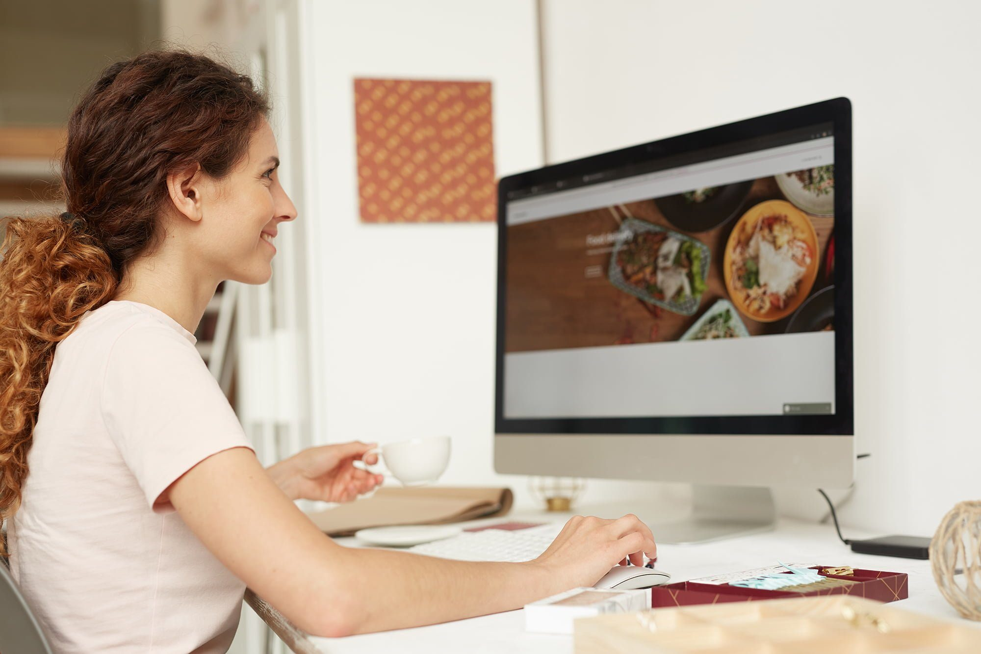 Positive attractive female web designer with curly hair sitting at table and drinking coffee while working on website in office